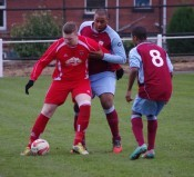 Yorkshire Amateur striker Craig Heard holds the ball up as Sam Jerome holds onto him