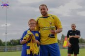 Garforth Town Legends captain Brett Renshaw collects the Ralph Backhouse Trophy from Ralph's great nephew Jack Yelland and presents him with a signed Miners jersey by the players involved in the game